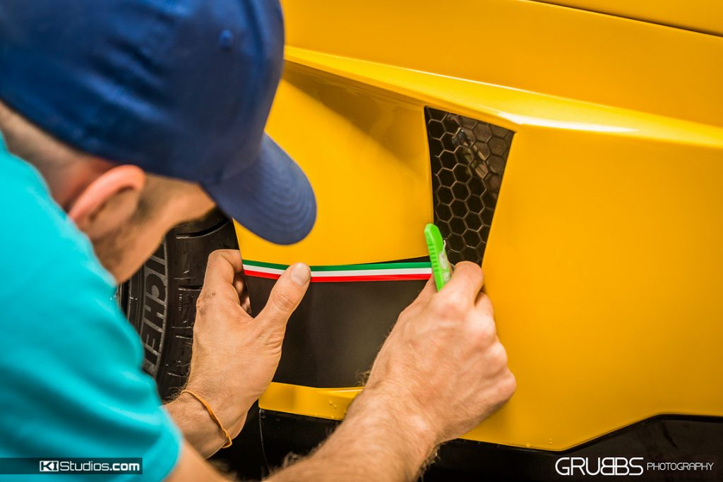 Kyle Isbell installing stripes on a Lamborghini